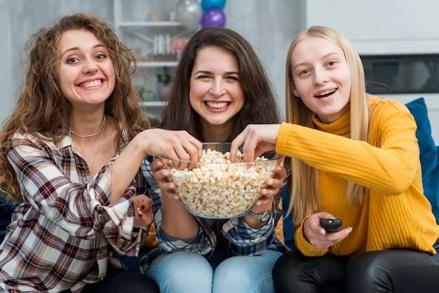 Amis en regardant un film en mangeant du pop-corn Photo gratuit