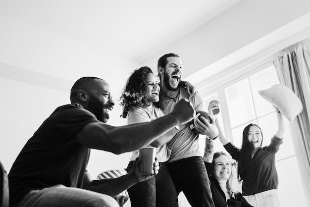 Amis en regardant le sport dans le salon Photo gratuit