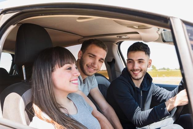 Amis s'amusant à l'intérieur de la voiture Photo gratuit
