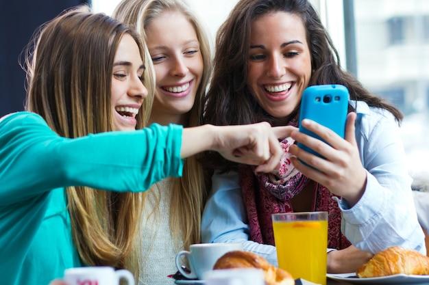 Amis s'amusant avec les smartphones Photo Premium