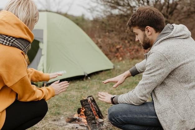 Des amis s'échauffent sur un feu de camp Photo gratuit
