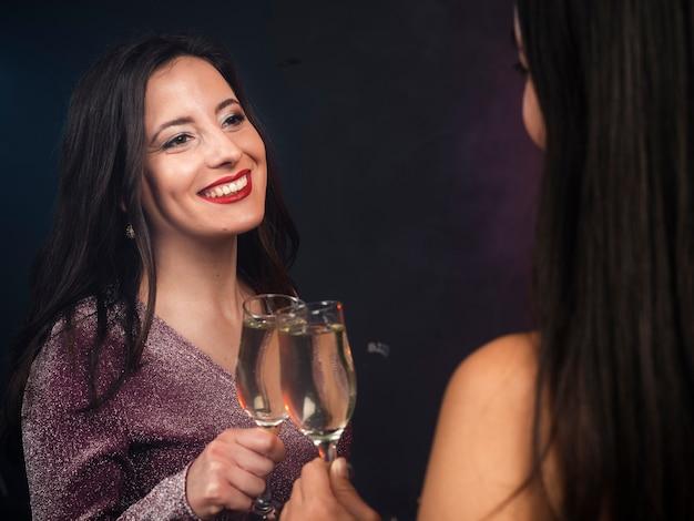 Amis se regardant avec du champagne à la fête du nouvel an Photo gratuit