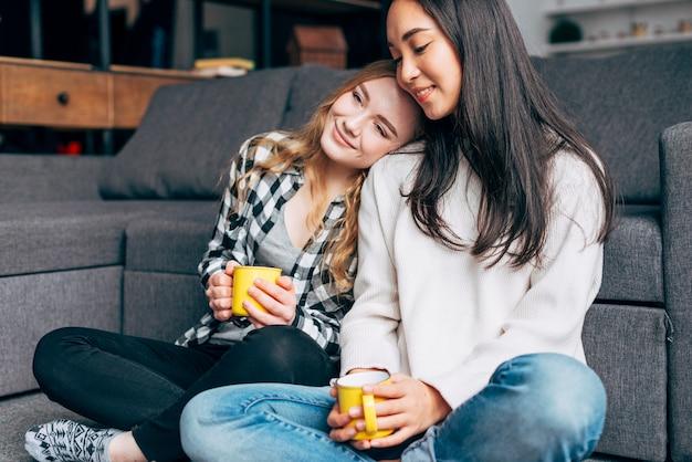 Amis Se Reposant Avec Des Tasses De Thé Photo gratuit