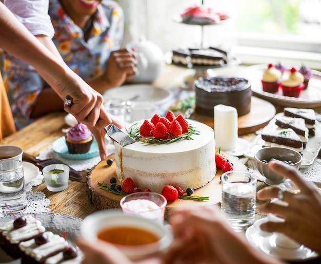 Amis se réunissant à la fête du thé manger des gâteaux plaisir de bonheur Photo gratuit