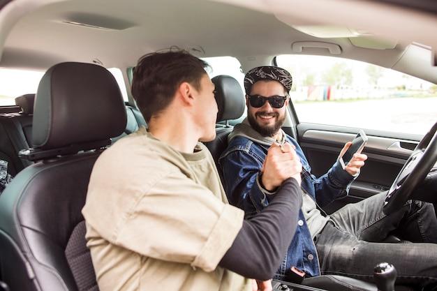 Amis se serrant la main dans la voiture Photo gratuit