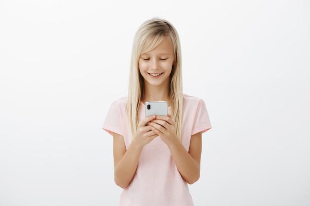 Les Amis Seront Jaloux Quand Verront Mon Nouveau Téléphone. Heureux Enfant Adorable Joyeux Aux Cheveux Blonds En T-shirt Rose, Tenant Un Smartphone, Riant, Regardant L'écran, Regardant Une Animation Drôle Sur Un Mur Gris Photo gratuit