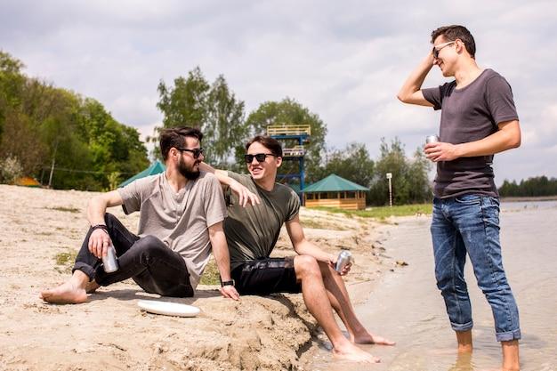 Amis de sexe masculin à lunettes de soleil assis sur la plage et parler Photo gratuit