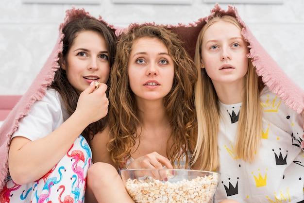 Amis en soirée pijama mangeant du pop corn Photo gratuit