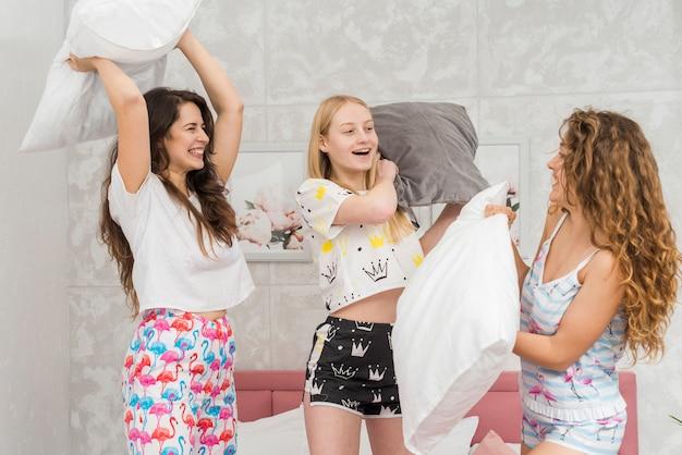 Amis en soirée pijama se battre avec des oreillers Photo gratuit