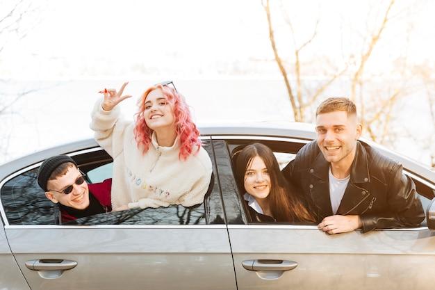 Amis souriants regardant par la fenêtre de la voiture Photo gratuit