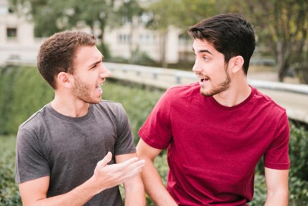 Amis en t-shirts parlant dans la rue Photo gratuit