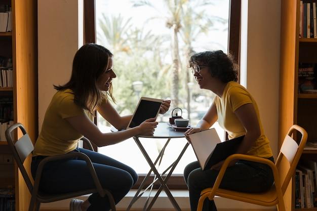 Amis avec tablette et livre rire dans la bibliothèque Photo gratuit