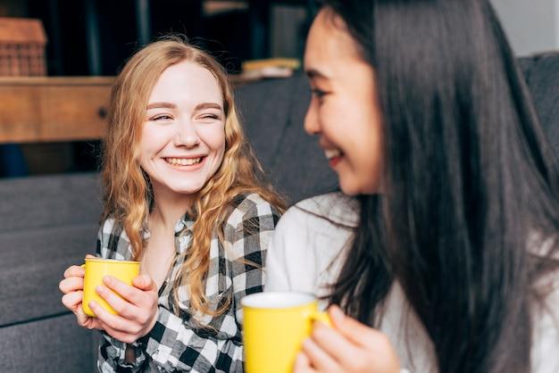 Amis avec des tasses à thé souriant Photo gratuit
