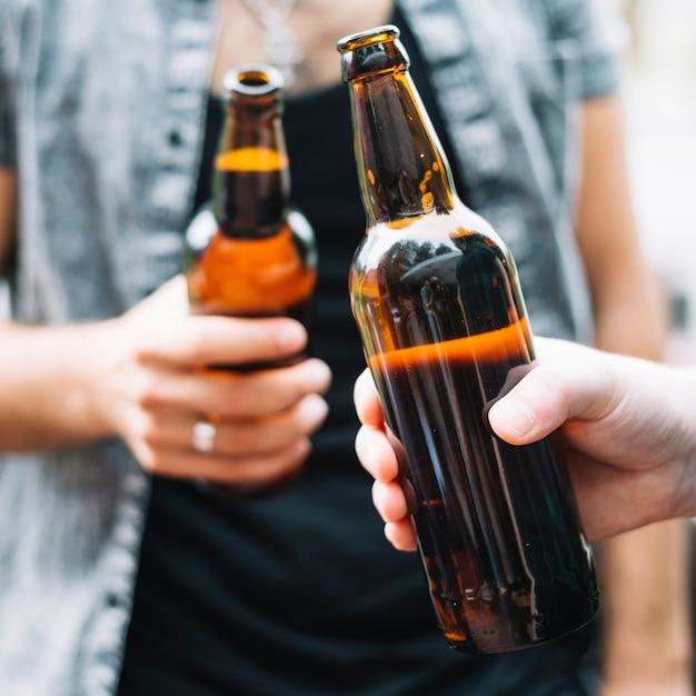 Amis tenant une bouteille de bière Photo gratuit