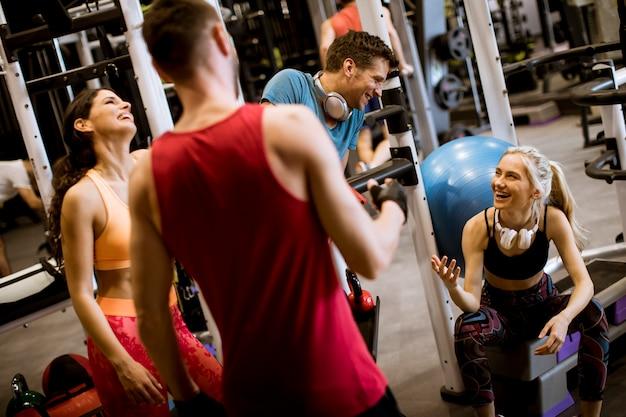 Amis en tenue de sport discutant ensemble dans une salle de sport après une séance d'entraînement Photo Premium