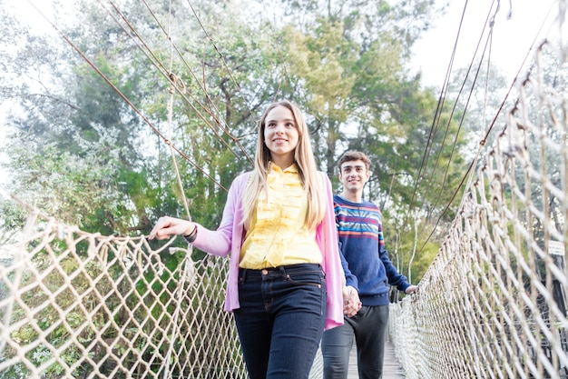 Amis Traversant Un Pont Dans Le Parc D'aventure Photo gratuit
