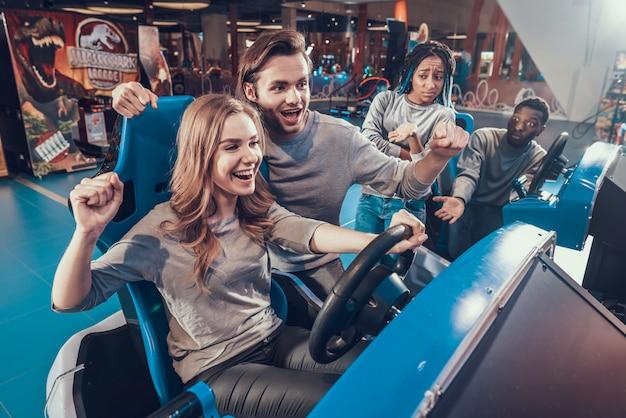 Amis sur les voitures bleues dans l'arcade une équipe gagne Photo Premium