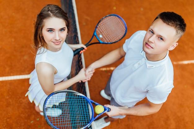 L'amitié gagne. deux jolies joueuses de tennis se serrant la main et souriant tout en se tenant près du filet de tennis. Photo Premium