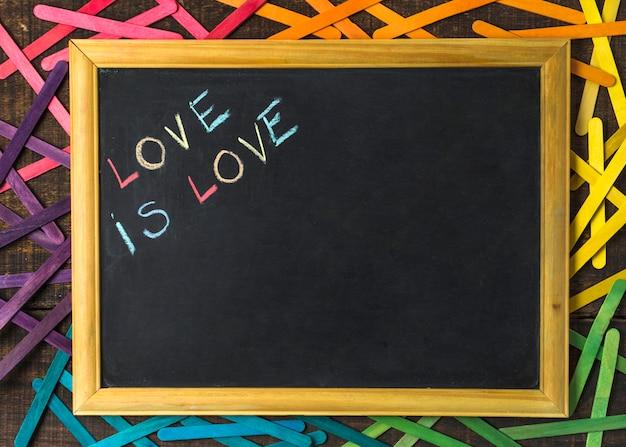 L'amour est mots d'amour au tableau parmi les bâtons aux couleurs lgbt Photo gratuit