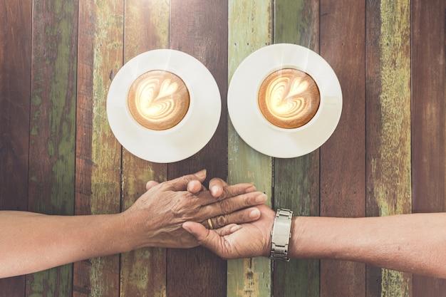 Amour de la main de couple ole dans un café Photo Premium