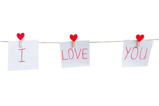 Amour rouge saint valentin épingles coeurs suspendus sur un cordon naturel isolé sur fond blanc. je t'aime inscription sur des morceaux de papier. Photo Premium