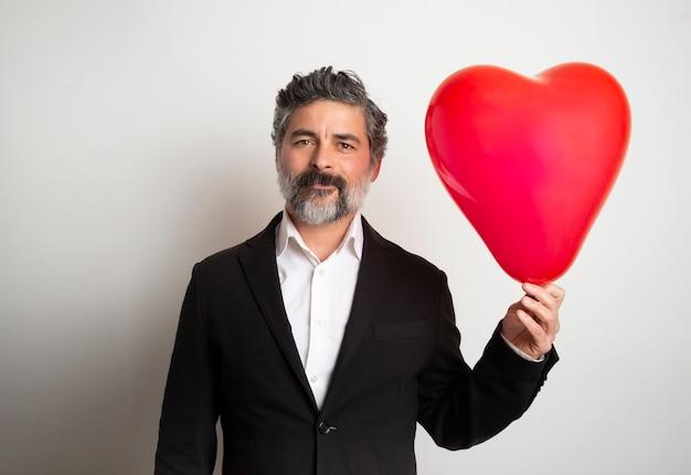 Amour Et Saint Valentin Homme Tenant Coeur Souriant Mignon Et Adorable Isolé. Homme De La Saint-valentin Avec Ballon à Air Rouge. Photo Premium