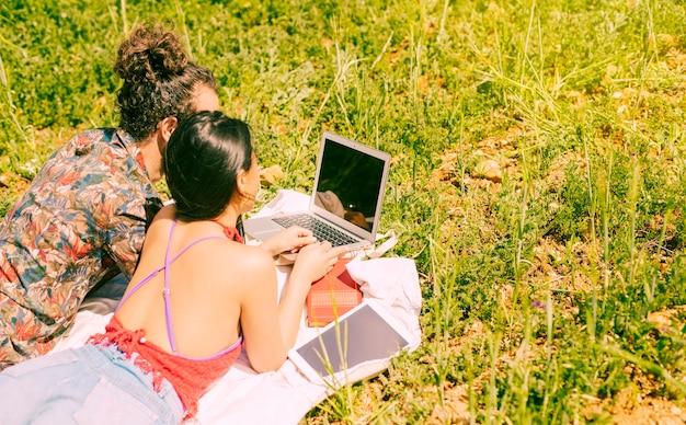 Amoureux à l'aide d'un ordinateur portable dans le champ Photo gratuit