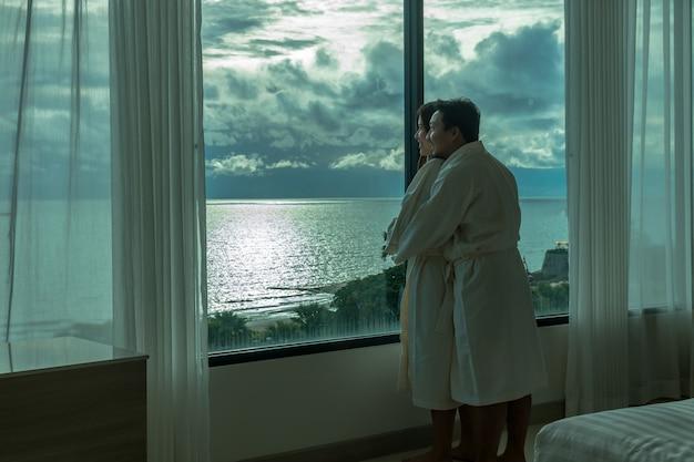 Amoureux asiatique en costume de peignoir étreignant et visitant la plage de la mer au réveil Photo Premium