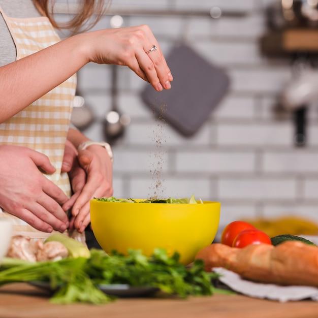 Amoureux préparant une salade de légumes dans la cuisine Photo gratuit