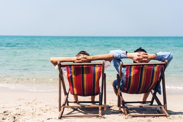 Amoureux romantique jeune couple relaxant assis sur la plage tropicale et regardant vers la mer. vacances d'été Photo Premium