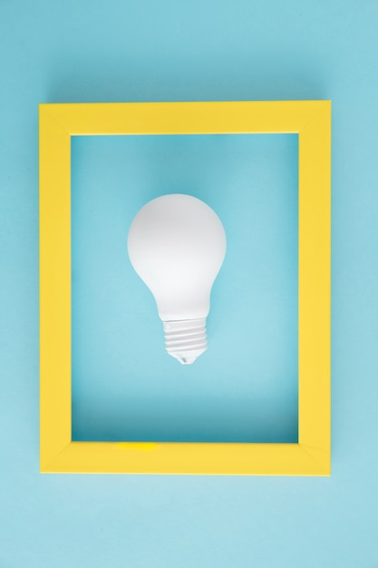 Ampoule blanche avec cadre jaune sur fond bleu Photo gratuit