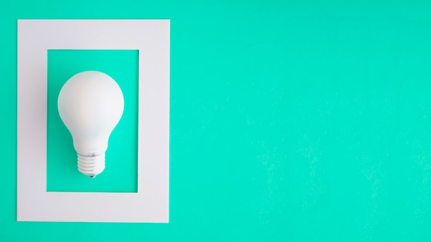 Ampoule blanche dans le cadre blanc sur fond vert Photo gratuit