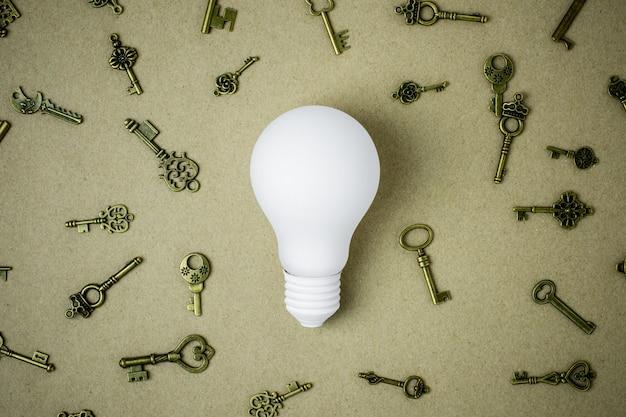 Ampoule blanche et nombreuses touches sur fond de papier brun Photo Premium