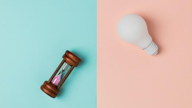 Ampoule blanche et un vieux sablier sur fond bleu et rose Photo Premium