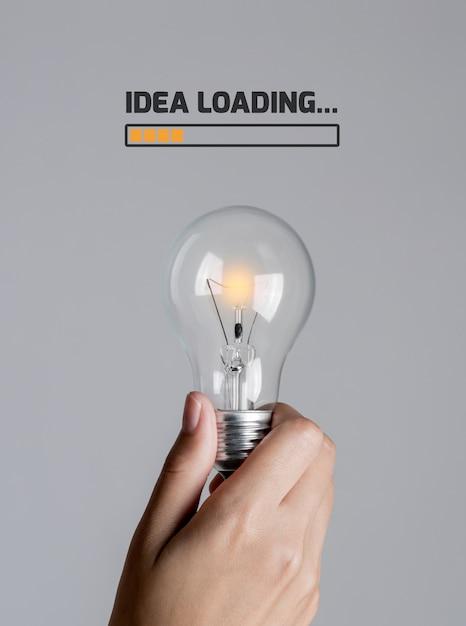 Ampoule commence progressivement allumer dans la main de la femme avec le texte Photo Premium