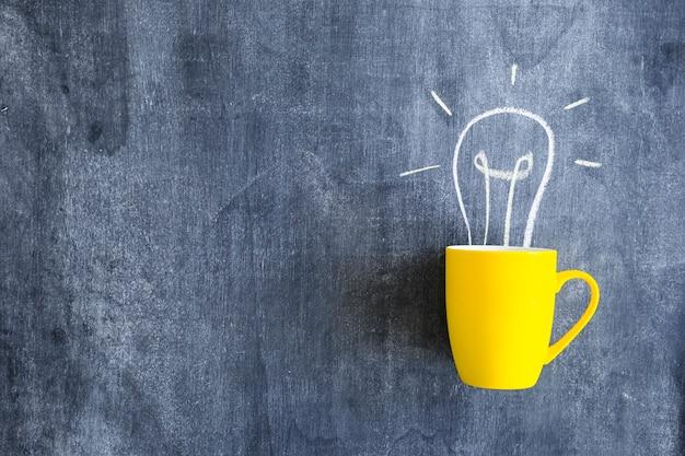 Ampoule dessinée sur la tasse jaune sur le tableau noir Photo gratuit