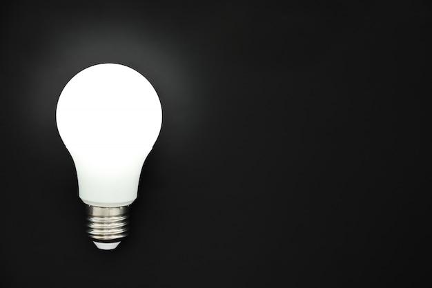 Ampoule led sur fond noir, concept d'idées, créativité, innovation ou économie d'énergie, espace copie, vue de dessus, pose plate Photo Premium