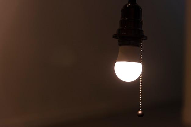 Une ampoule lumineuse suspendue dans une pièce Photo gratuit