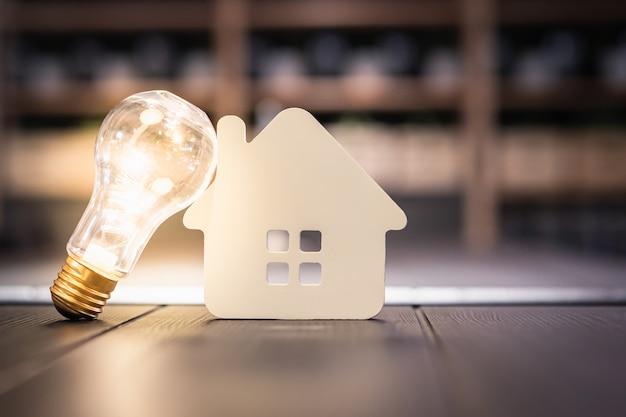 Ampoule Avec Maison En Bois Sur La Table, Photo Premium