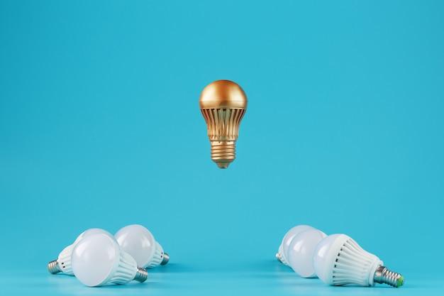 Une Ampoule D'or Proéminente Lévite Au-dessus D'un Environnement D'ampoules à Led Blanches. Photo Premium