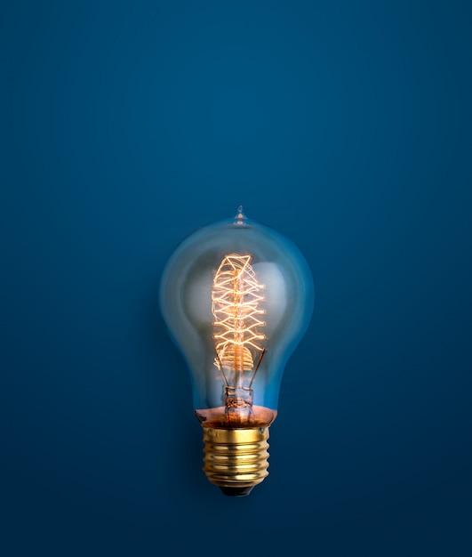Ampoule rougeoyant sur le concept de fond des idées créatives fond bleu. Photo Premium