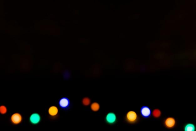 Ampoules défocalisés colorés sur fond noir Photo gratuit