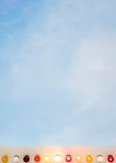 Ampoules lumineuses colorées contre le ciel bleu Photo gratuit