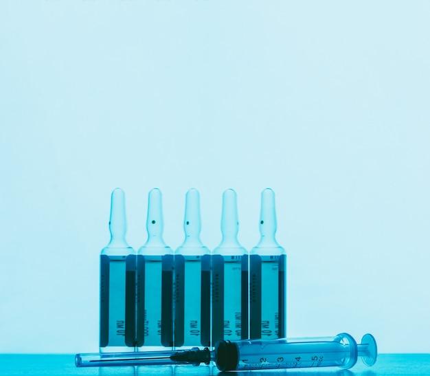 Les ampoules avec la solution pour les injections et la seringue jetable sur un fond bleu Photo Premium