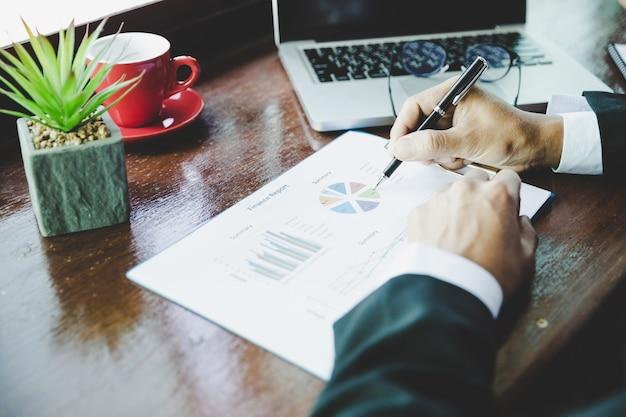 Analyse d'un homme d'affaires travaillant à discuter des tableaux et des graphiques montrant les résultats. Photo gratuit