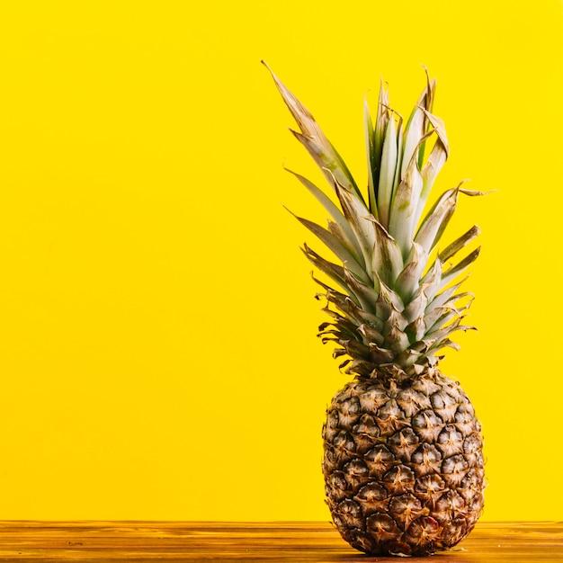 Ananas entier sur la table sur fond jaune Photo gratuit