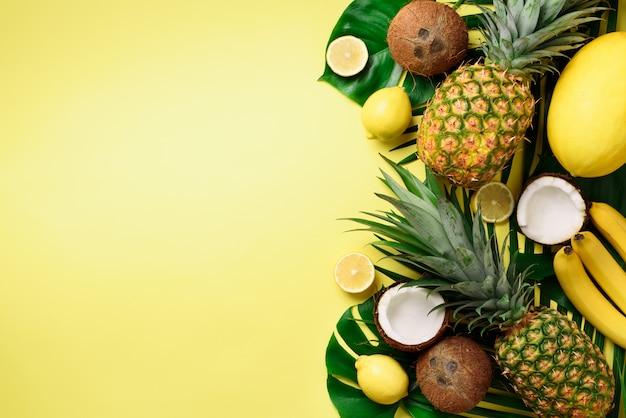 Ananas exotiques, noix de coco mûres, banane, melon, citron, palmier tropical et feuilles de monstera vert Photo Premium