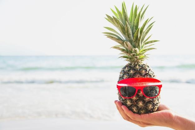 Ananas frais mettant des verres dans les mains d'un touriste avec la vague de la mer Photo gratuit
