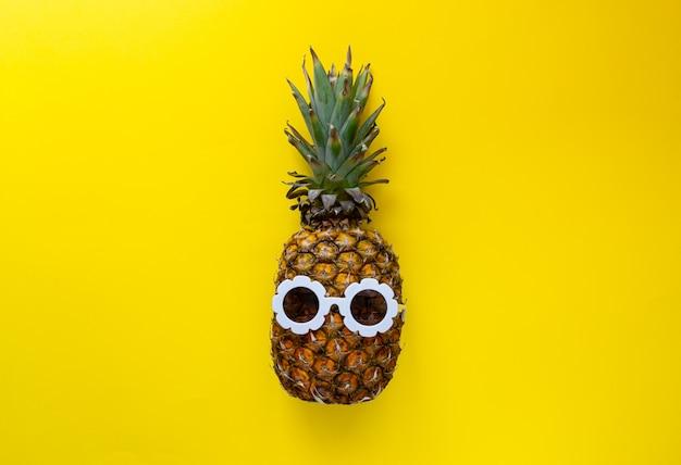 Ananas à lunettes de soleil blanches sur le fond coloré, concept créatif de l'été Photo Premium