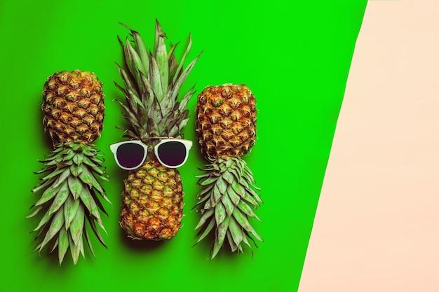 Ananas sur papier de couleur avec des lunettes Photo Premium